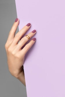 회색 바탕에 보라색 종이 배너를 들고 단정 한 여자의 손. 비즈니스 사무실 미용실 템플릿입니다.
