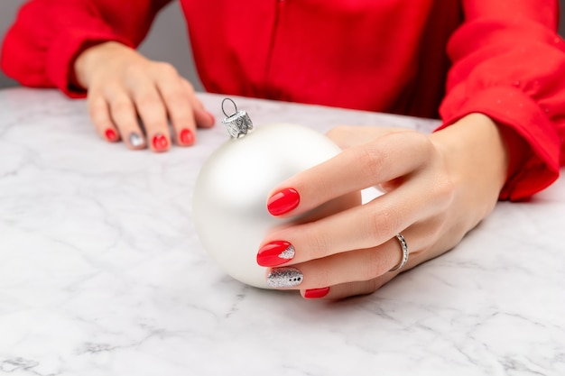大理石の灰色の背景にクリスマスのネイルデザインで手入れの行き届いた女性の手
