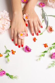 꽃과 빨간 매니큐어로 깔끔한 여성의 손. 프리미엄 사진
