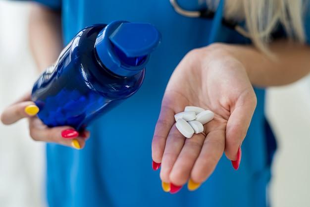 病院の廊下で錠剤を持っている看護師の手入れの行き届いた若い手。医学の概念