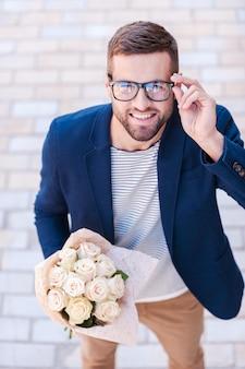 あら、御機嫌よう!花の花束を保持し、屋外に立っている間彼の眼鏡を調整するスマートカジュアルウェアの陽気な若い男の上面図