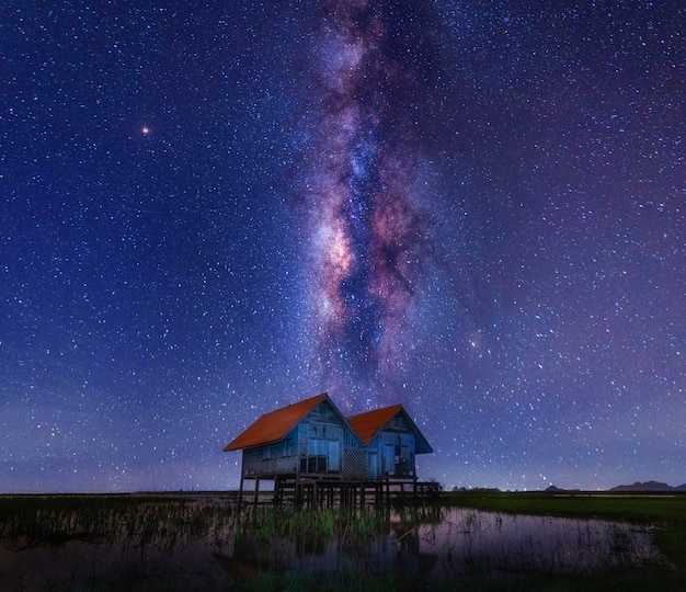 The well known twin house at talaynoi,pattarung. with milky way in a middle of night sky and reflection of the house on water background .