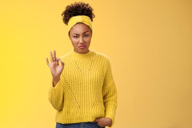悪くはない。肖像画真面目な見た目自信のある傲慢な若いアフリカ系アメリカ人女性は努力に同意します良いショー大丈夫ok通常のジェスチャー独善的な承認、立っている黄色の背景に感銘を受けました。コピースペース