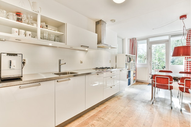 Well organized small home kitchen interior with sink and light furniture with stove in urban apartment