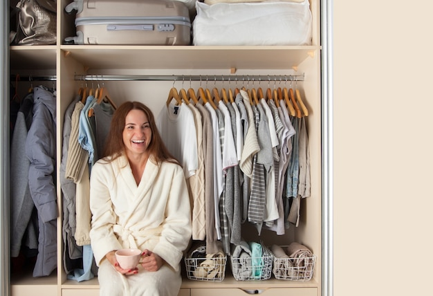 Well-organized wardrobe. clothes storage. the girl sits in the closet and laughs.