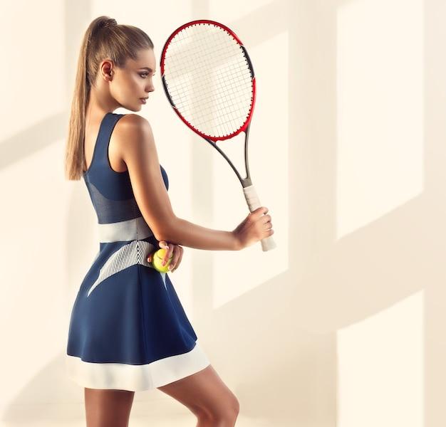長いポニーテールの髪型とトレンディなメイクの形の良いスポーティな女性がテニスラケットを持っており、身体活動の魅力を示しています。スポーツ、テニス、美容、ファッション。