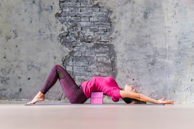 Well-shaped sporty young woman training in gym using block