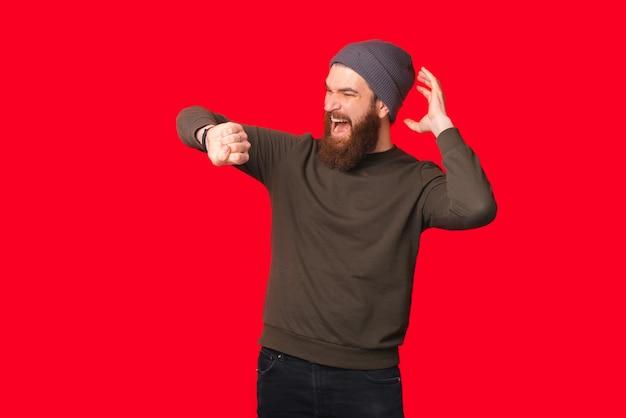 驚いたあごひげを生やした男が腕時計を見ています。
