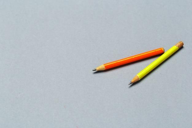 Хорошо потертые желтые карандаши на светло-сером фоне