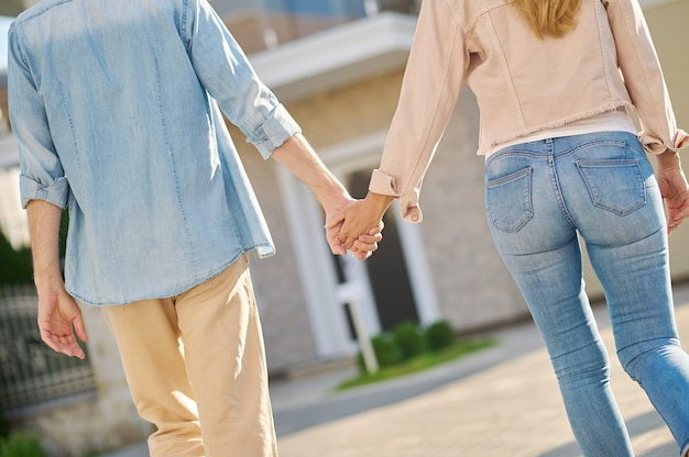 안녕. 화창한 날 집으로 걸어가는 손을 잡고 데님 옷을 입은 남녀의 뒷모습