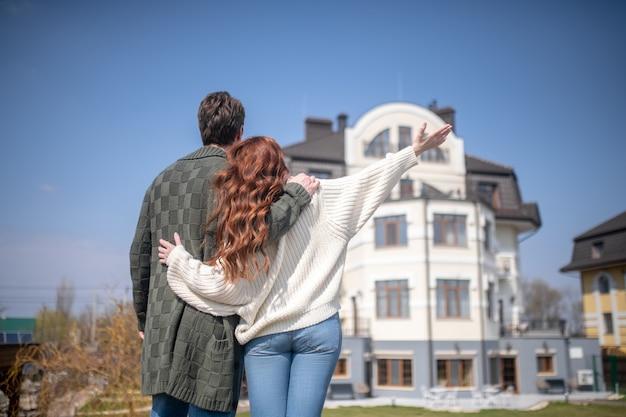 幸福。晴れた日に新しい家の背景に背を向けて立っている幸せな男と女を抱き締める