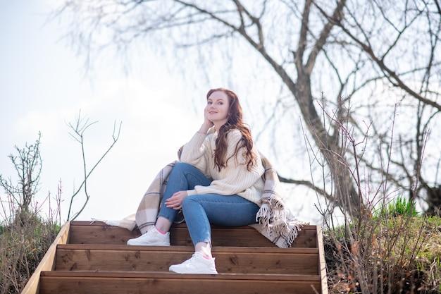 幸福、気分。春の日に自然の中で階段に座っているセーターとジーンズで物思いにふける若い女性の笑顔