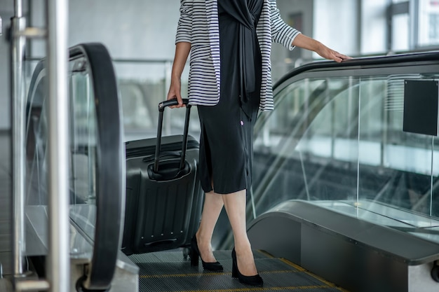 Wellbeing. woman in black dress on high heels with suitcase on wheels climbing up escalator to airport, without face