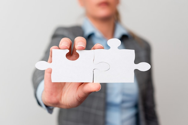 Welldressed business woman holding two pieces of jigsaw puzzle professional adult women resolving mi