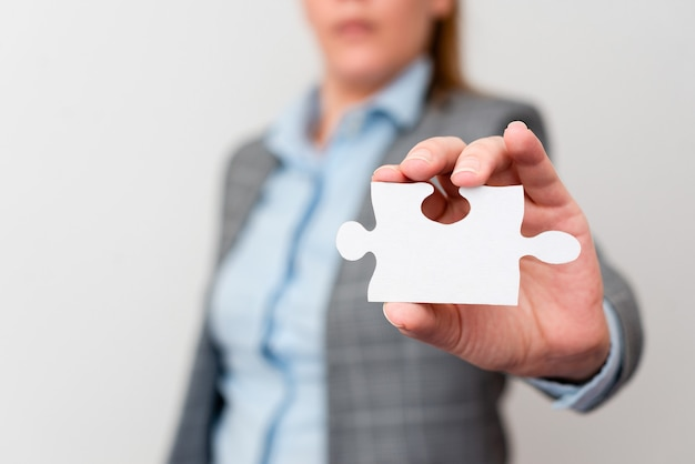 Welldressed business woman holding two pieces of jigsaw puzzle, professional adult women resolving missing ideas, strategy for new ideas