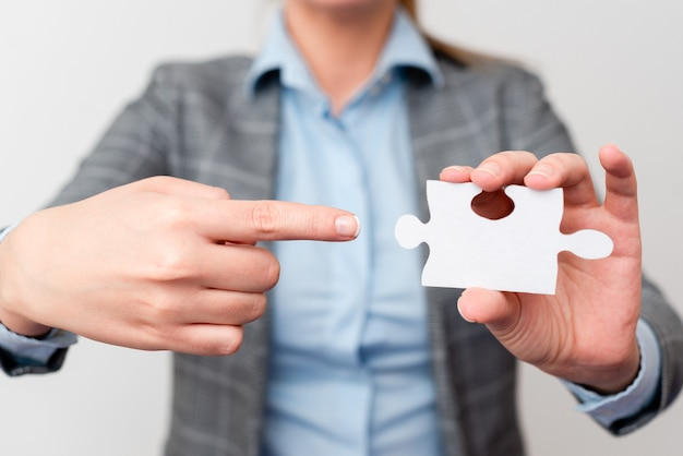 Welldressed business woman holding two pieces of jigsaw puzzle, professional adult women