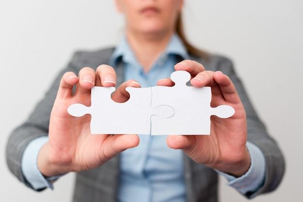 Хорошо одетая деловая женщина, держащая две части пазла, профессиональные взрослые женщины, решающие отсутствующие идеи, стратегия для новых идей