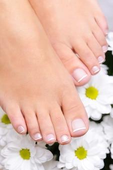 フランスのペディキュアと花で手入れの行き届いた女性の足