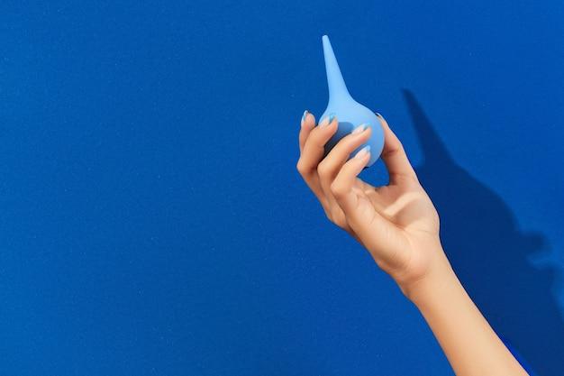 青い背景に浣腸を持っている手入れの行き届いた女性の手