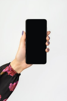 Wellgroomed womans hand holding smartphone on gray background