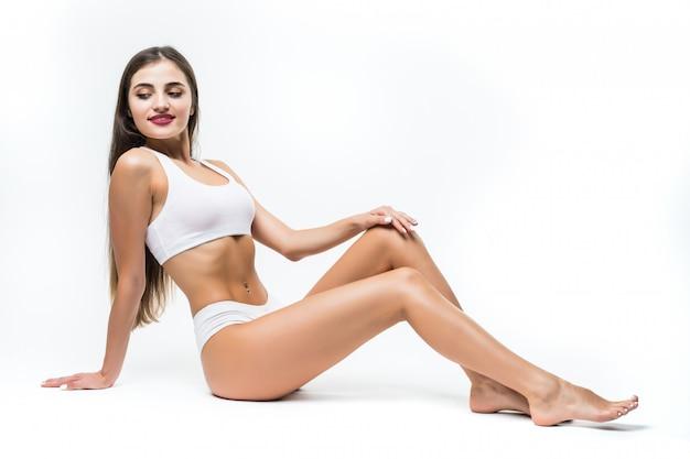 건강과 미용 개념. 흰색 바닥에 앉아 흰 속옷에 아름 다운 슬림 여자