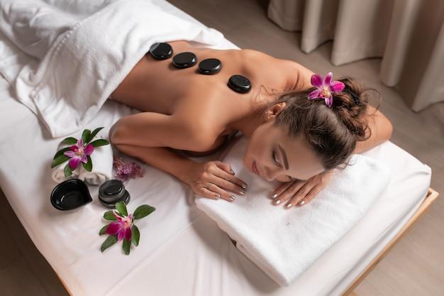 Оздоровление, красота и концепция релаксации - красивая молодая женщина, имеющая массаж горячими камнями в спа-салоне