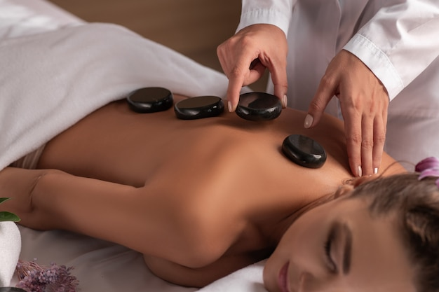 Wellness, beauty and relaxation concept - beautiful young woman having hot stone massage at spa