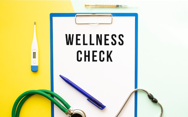 Wellness check text on a letterhead in a medical folder on a beautiful background. stethoscope, thermometer and pen.