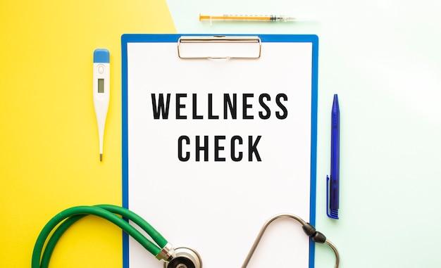 웰니스 체크는 아름다운 배경의 의료 폴더에 있는 레터헤드에 있는 텍스트입니다.