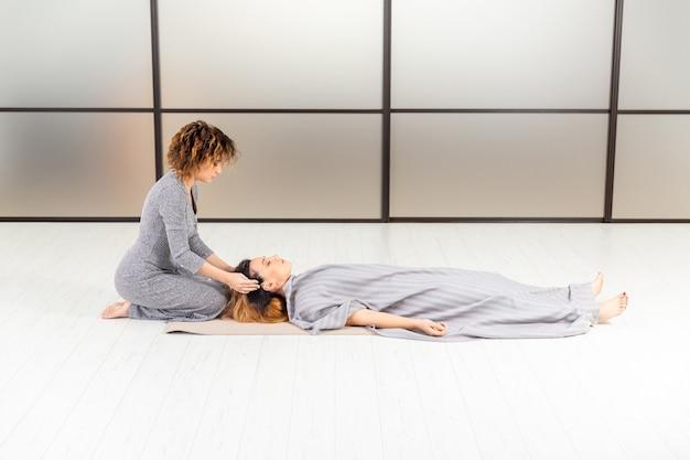 ウェルネス健康コンセプト。床にいる2人の女性の瞑想。白い部屋でリラックスして禅を。ボディケア。