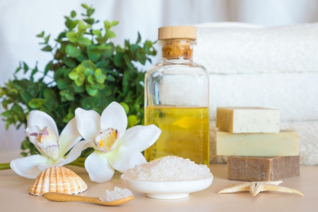 Wellness setting. sea salt, soap, towel, oil and flowers on wooden background