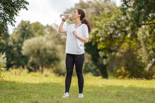 Велнес. спортивная женщина в спортивной одежде, пить бутылку воды. на заднем плане летний зеленый парк Premium Фотографии