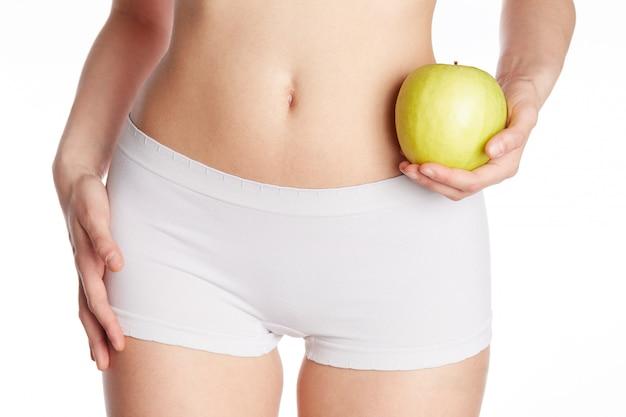 Wellness woman holding a green apple
