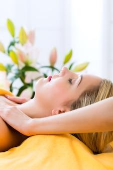 Велнес - женщина получает массаж головы или лица в спа