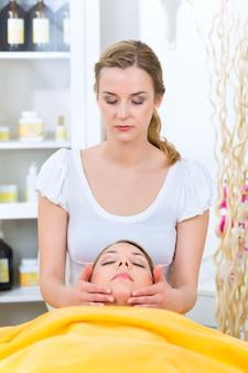 ウェルネス-スパで頭または顔のマッサージを受けている女性