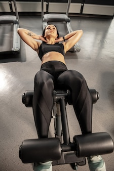 Wellness. young muscular caucasian woman practicing in gym with equipment. athletic female model doing abs exercises, training her upper body, belly. wellness, healthy lifestyle, bodybuilding.