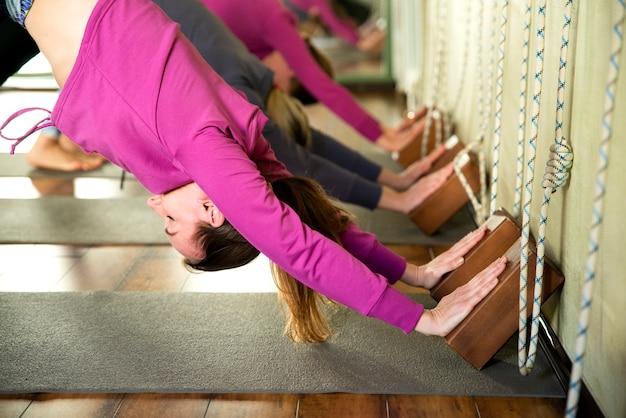 Занятия йогой, группа людей ослабляя и делая представление йоги против стены. wellness и здоровый образ жизни.