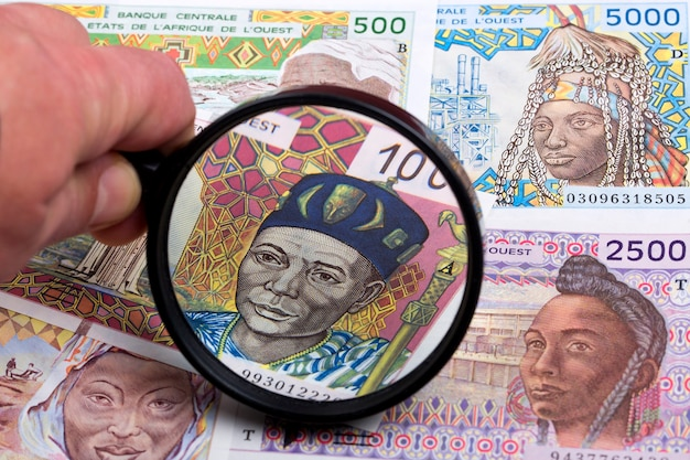 West african money in a magnifying glass