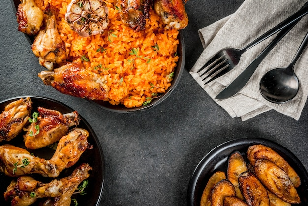 West african national cuisine. jollof rice with grilled chicken wings and fried bananas plantains
