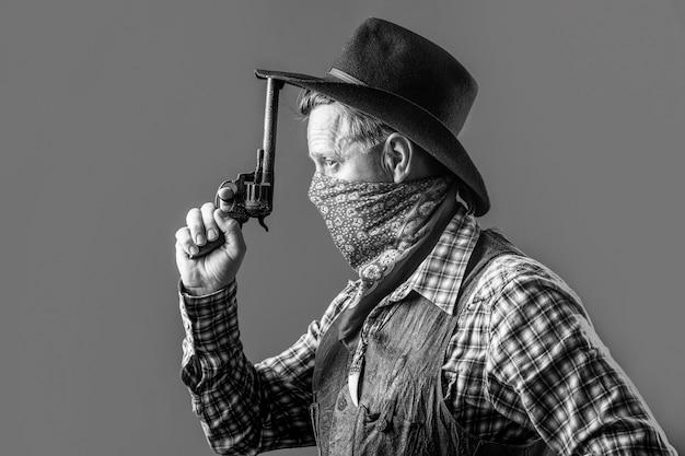 서쪽, 총. 카우보이의 초상화입니다. 마스크를 쓴 미국 산적, 모자를 쓴 서부 남자. 모자에 카우보이의 초상화입니다. 카우보이 모자, 총을 입고 남자의 초상화입니다. 카우보이의 초상화입니다. 검정색과 흰색.