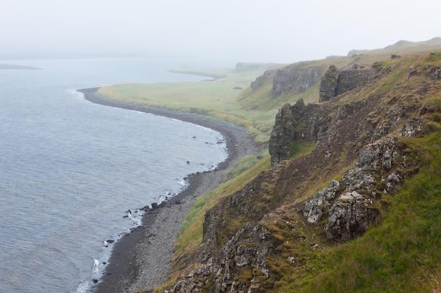 霧深い天候の西アイスランドの海の海岸線
