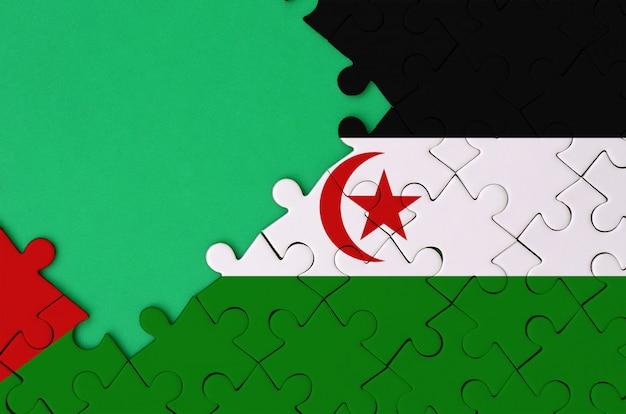 서쪽 사하라 국기는 왼쪽에 무료 녹색 복사 공간이있는 완성 된 직소 퍼즐에 그려져 있습니다.