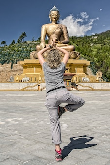 Western tourist from behind with blond wavy hair in vertical yoga position on the explanda in front of the buddha dordenma statue in buthan.the tallest buddha in the world. golden buddha. grey clothes