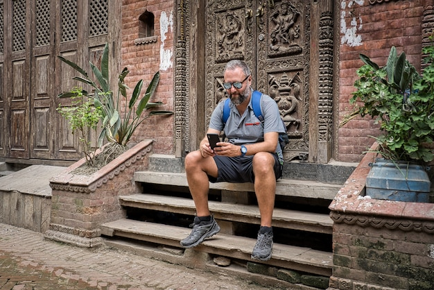 Western tourist with gray color shorts, mirror sunglasses and blue shirt sitting on the street next to a carved wooden door in nepal is checking the smartphone. lifestile, travel and tecnology concept