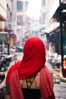Western woman covered in a red scarf exploring varanasi