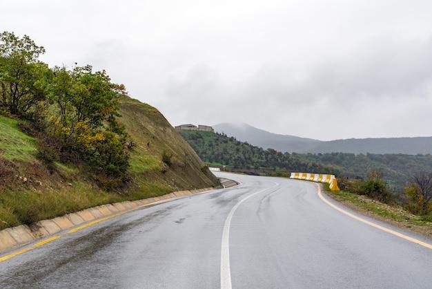 Мокрая асфальтовая дорога в гористой местности