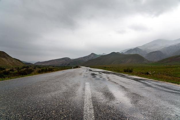 Wet asphalt road in mountainous area