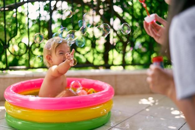젖은 아기는 작은 팽창식 수영장에 앉아 엄마가 내뿜는 비눗방울을 잡습니다.