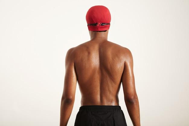 Schiena bagnata e testa di un giovane nuotatore afroamericano muscoloso in berretto rosso