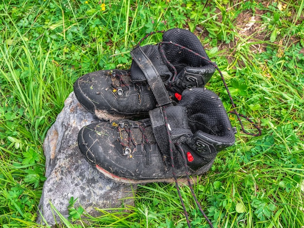 Wet black hiking boots dry on a stone against the background of green grass. difficulties of hiking, drying clothes in nature.
